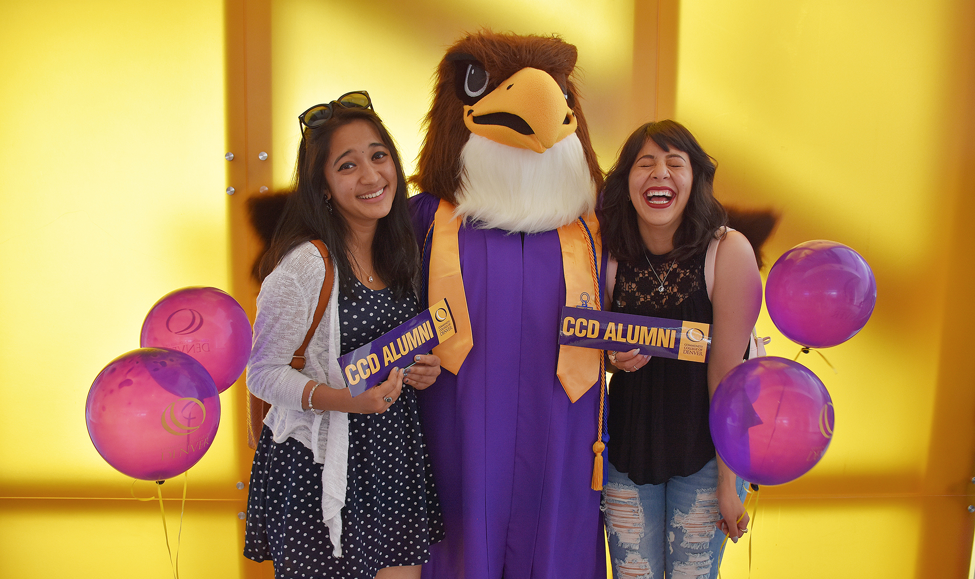 Two CCD Students holding an Alumni bumpersticker with the mascot