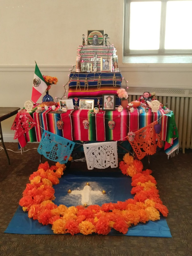 Dia De Los Muertos Alter with orange flowers and many decorative items