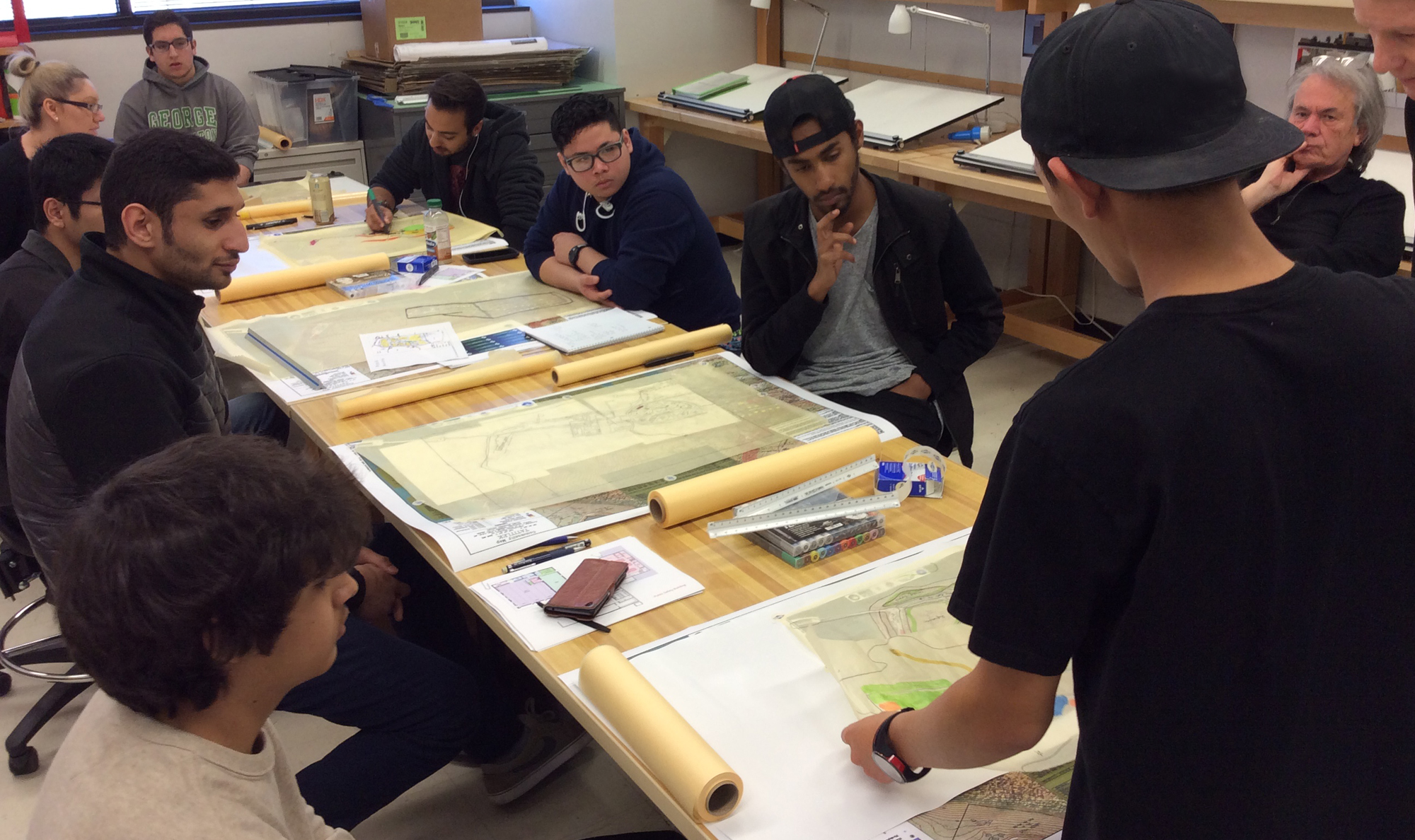 students around a design table with drafting designs