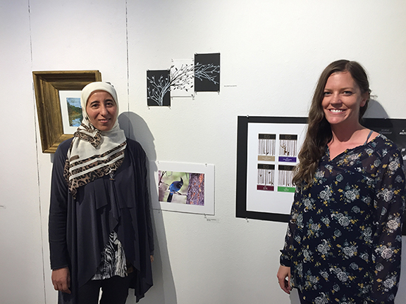 two women standing in an art gallery smiling