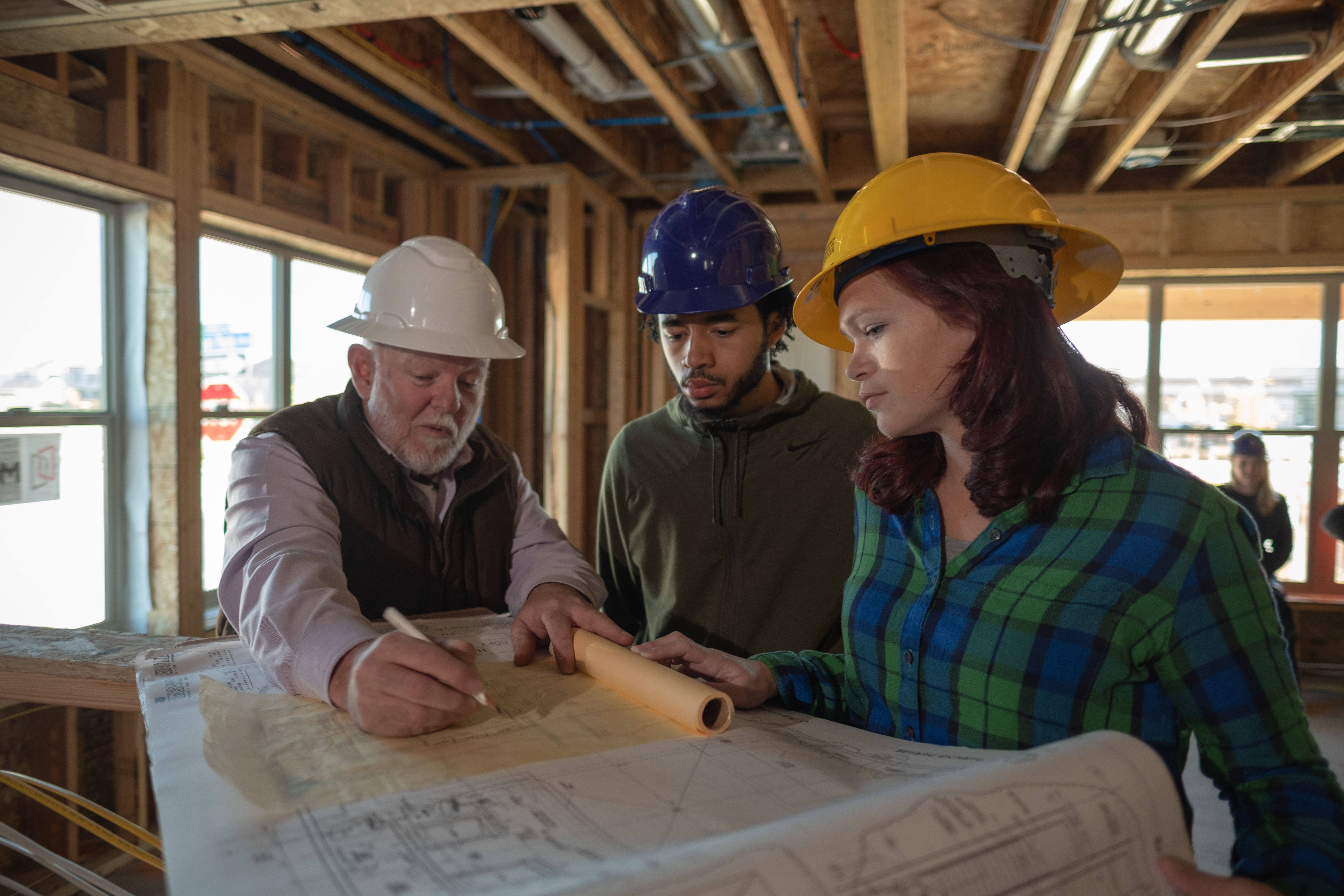 two students with professor at a construction site