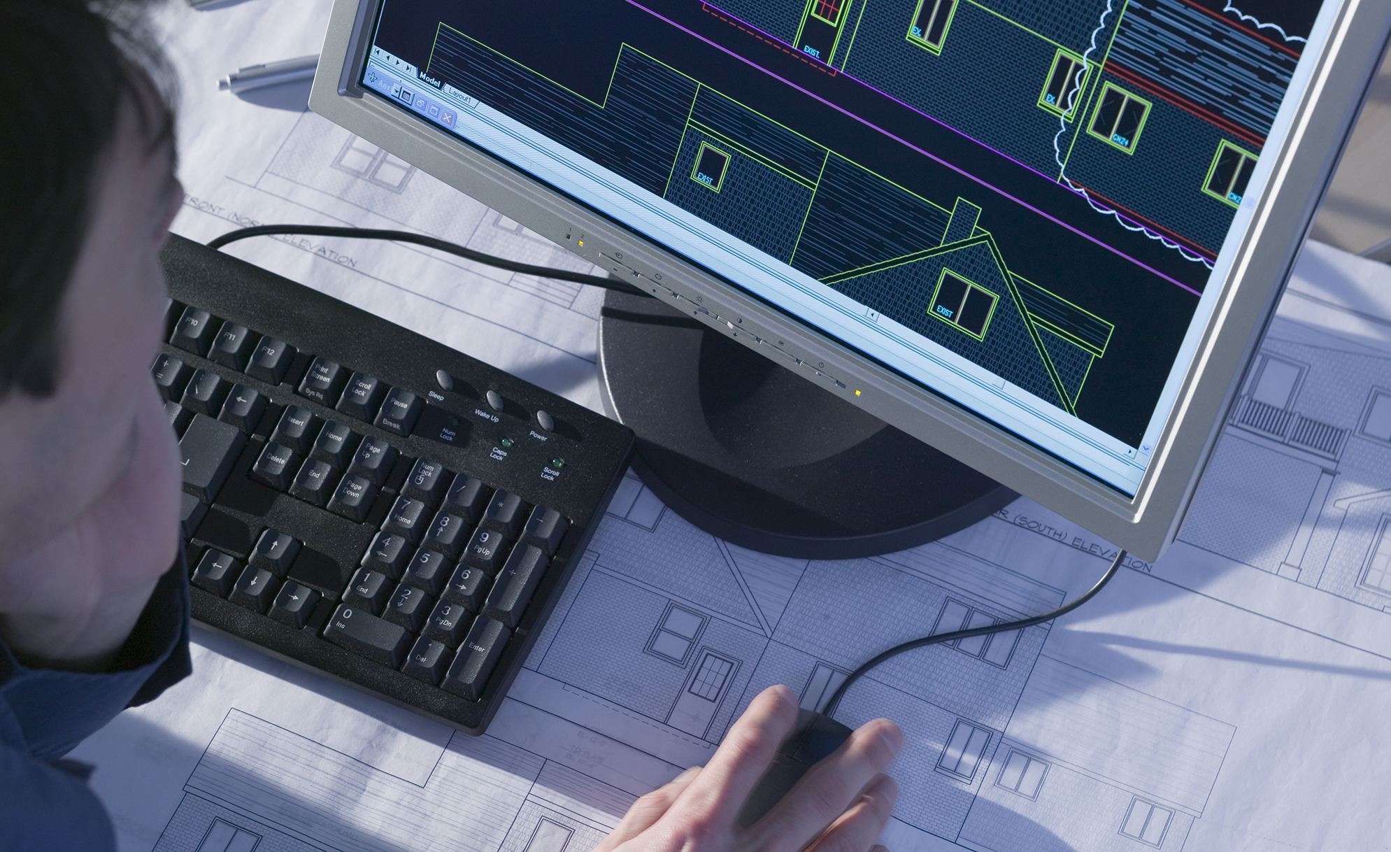 image of the hands of a male student working on computer drafting and blueprints.