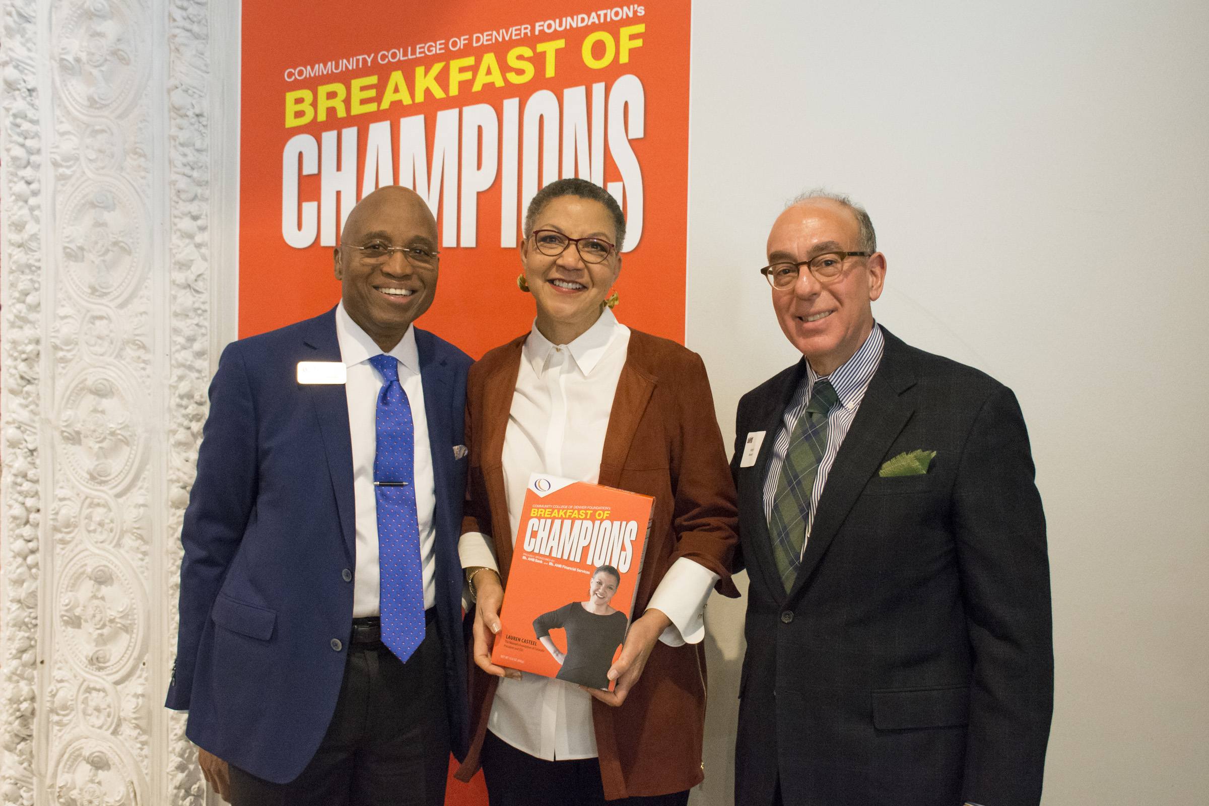 woman holding a Breakfast of Champions cereal box next to two men in suits