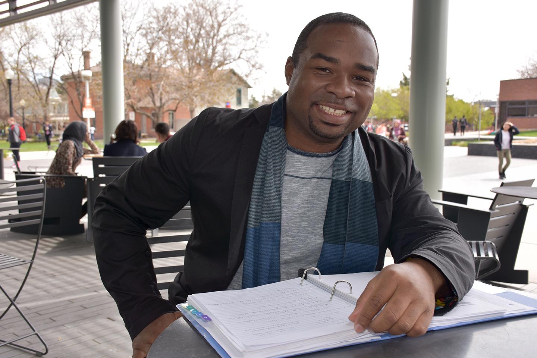 black man at a table smiling