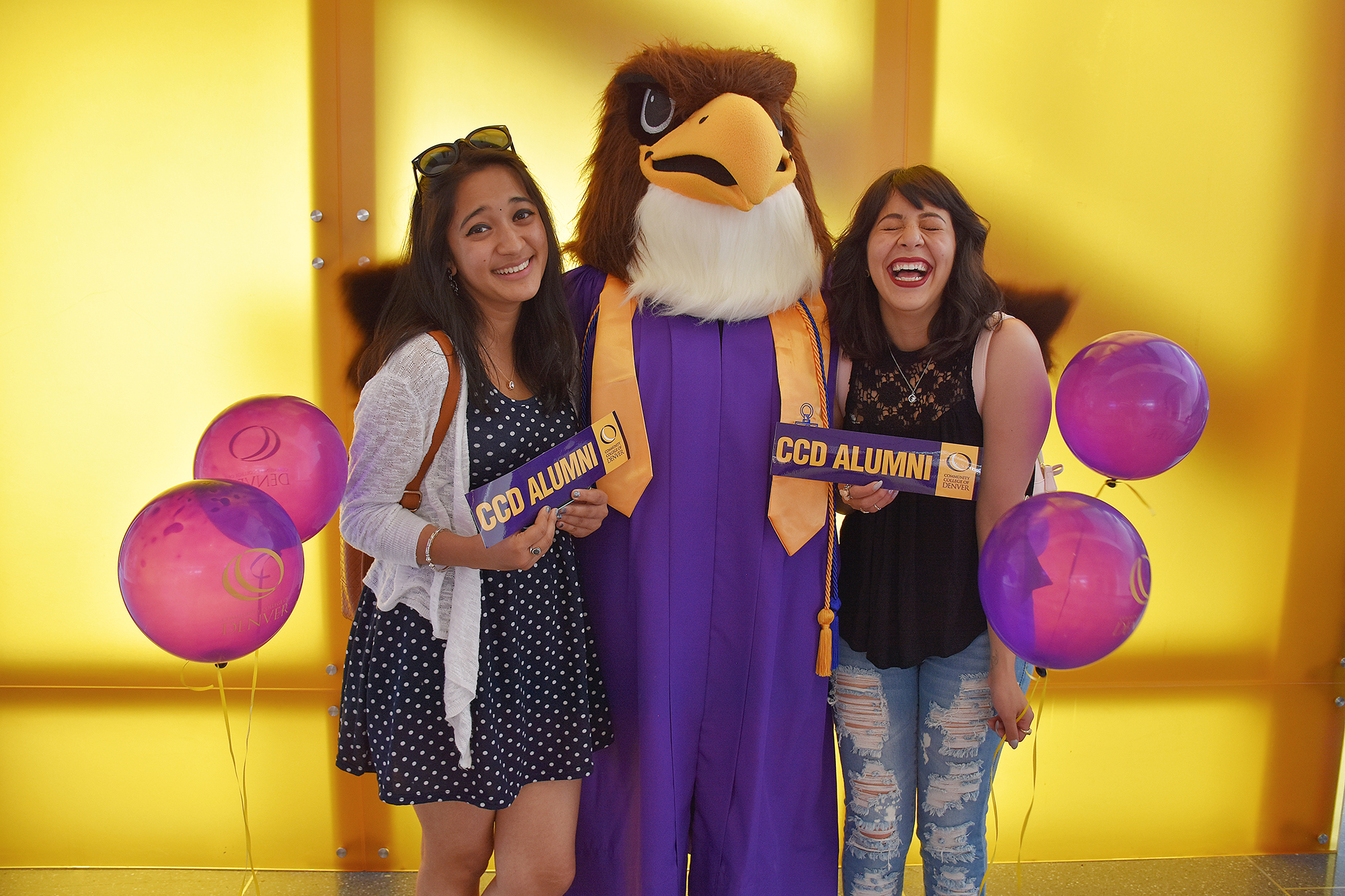 two women holding CCD Alumni bumperstickers with Mascot