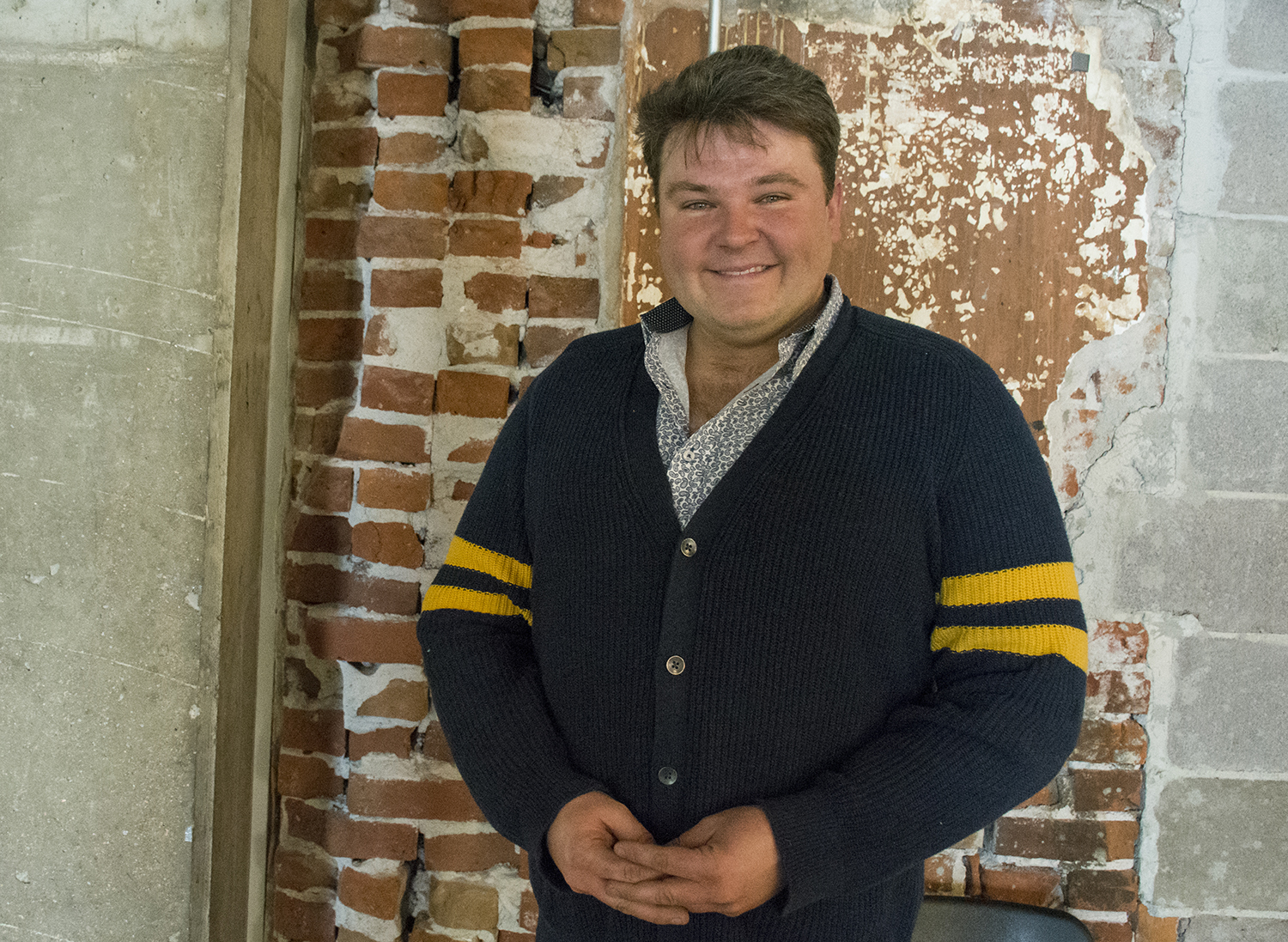 while male standing in front of a brick wall with his hands folded smiling