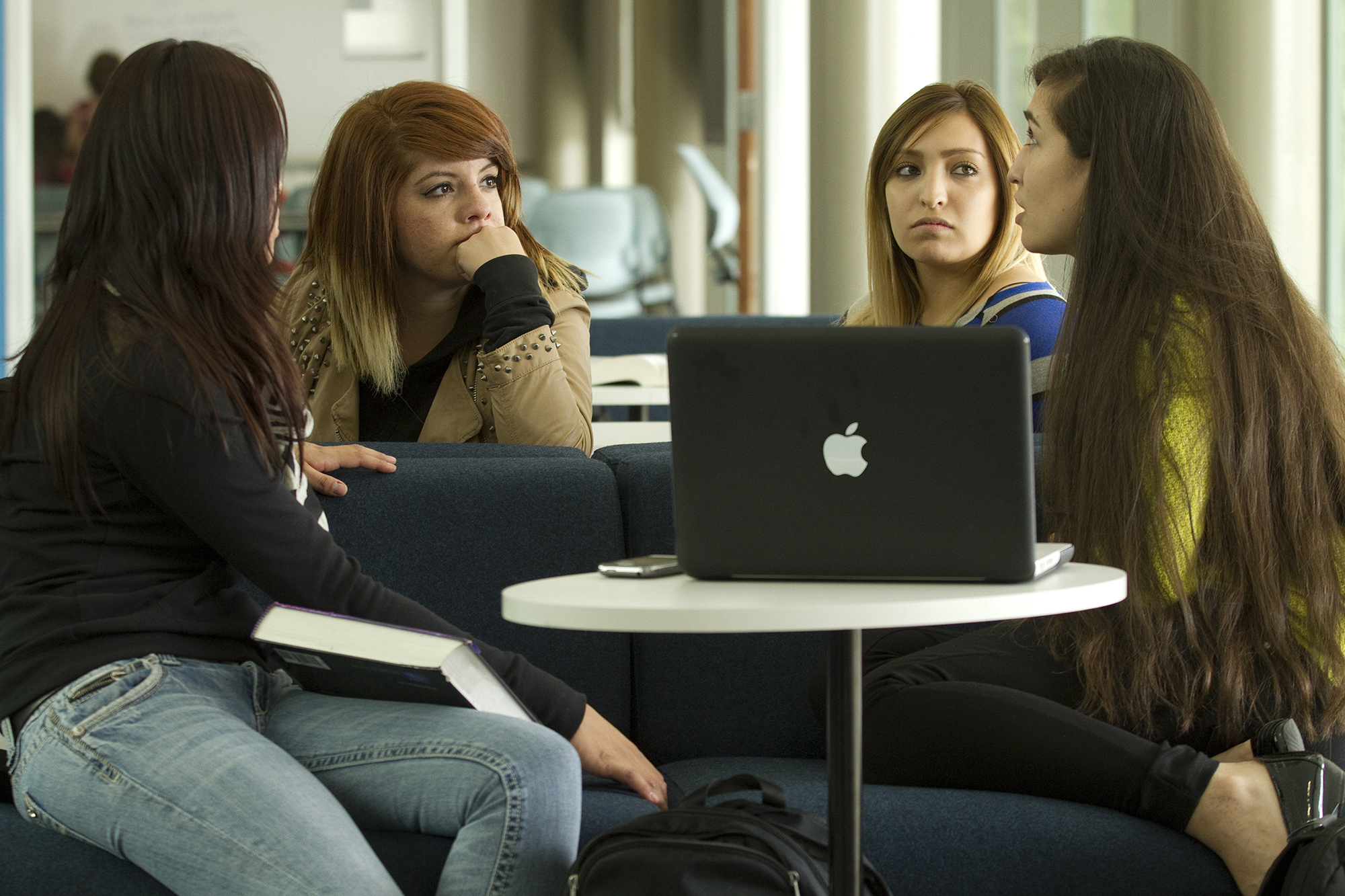 Four female students having a serious discussion in the Confluence building.