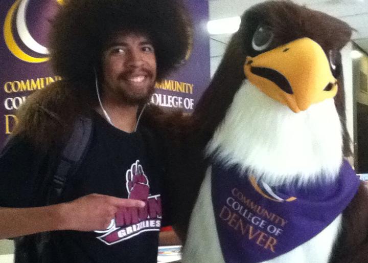 black man standing next to CCD mascot Swoop