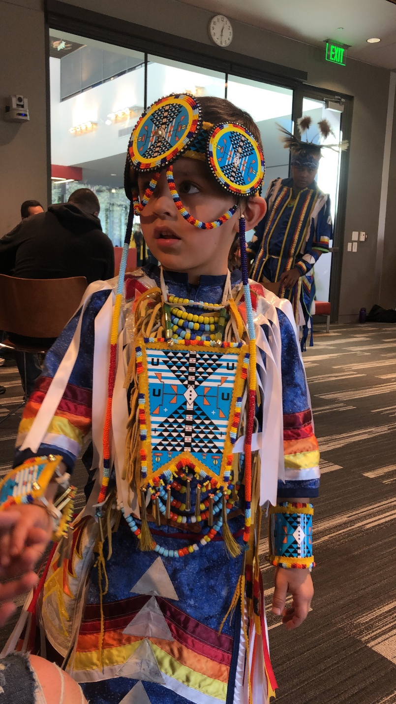 young boy dressed in colorful traditional native wear