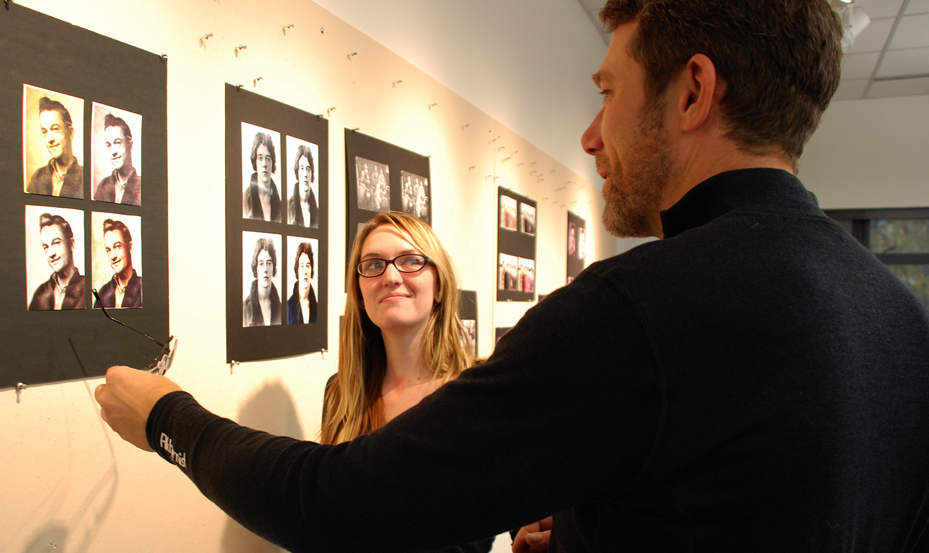 man and woman discuss the graphic image on the wall created by graphic designer