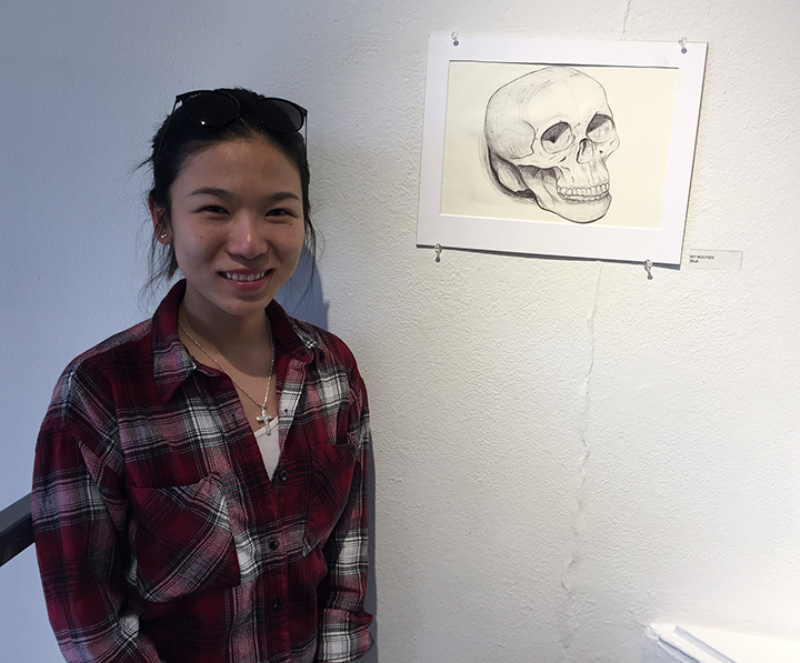 woman standing in front of a drawing of a skull