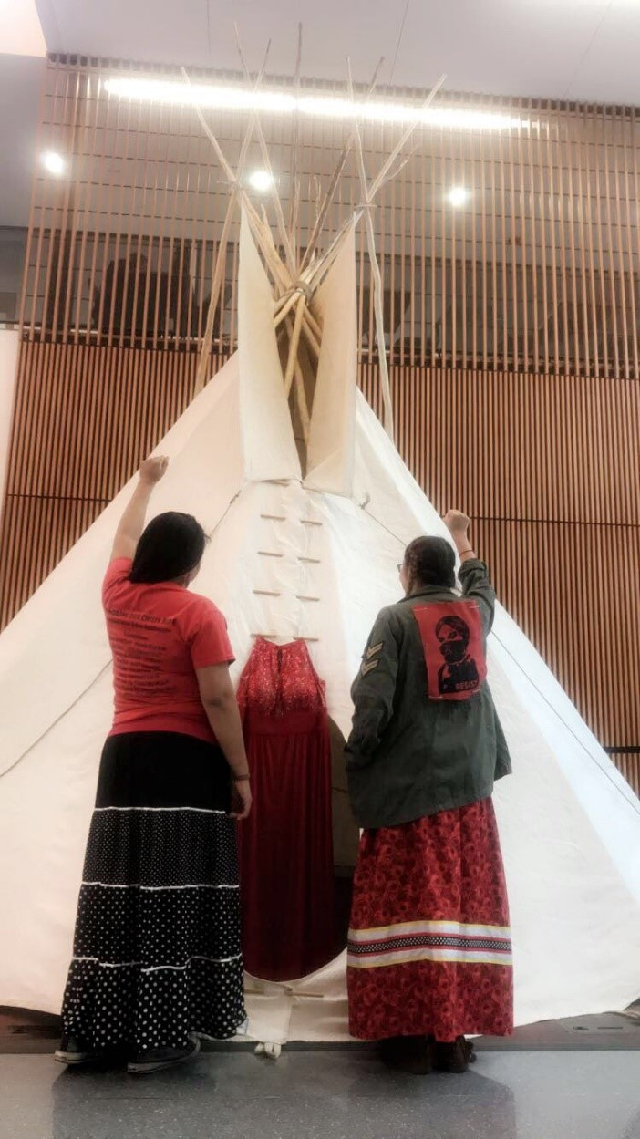 Two Females with fists raised in front of a tipi
