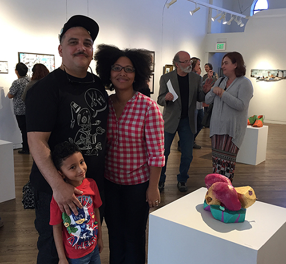 man standing with a woman and 5-year old boy in an art gallery
