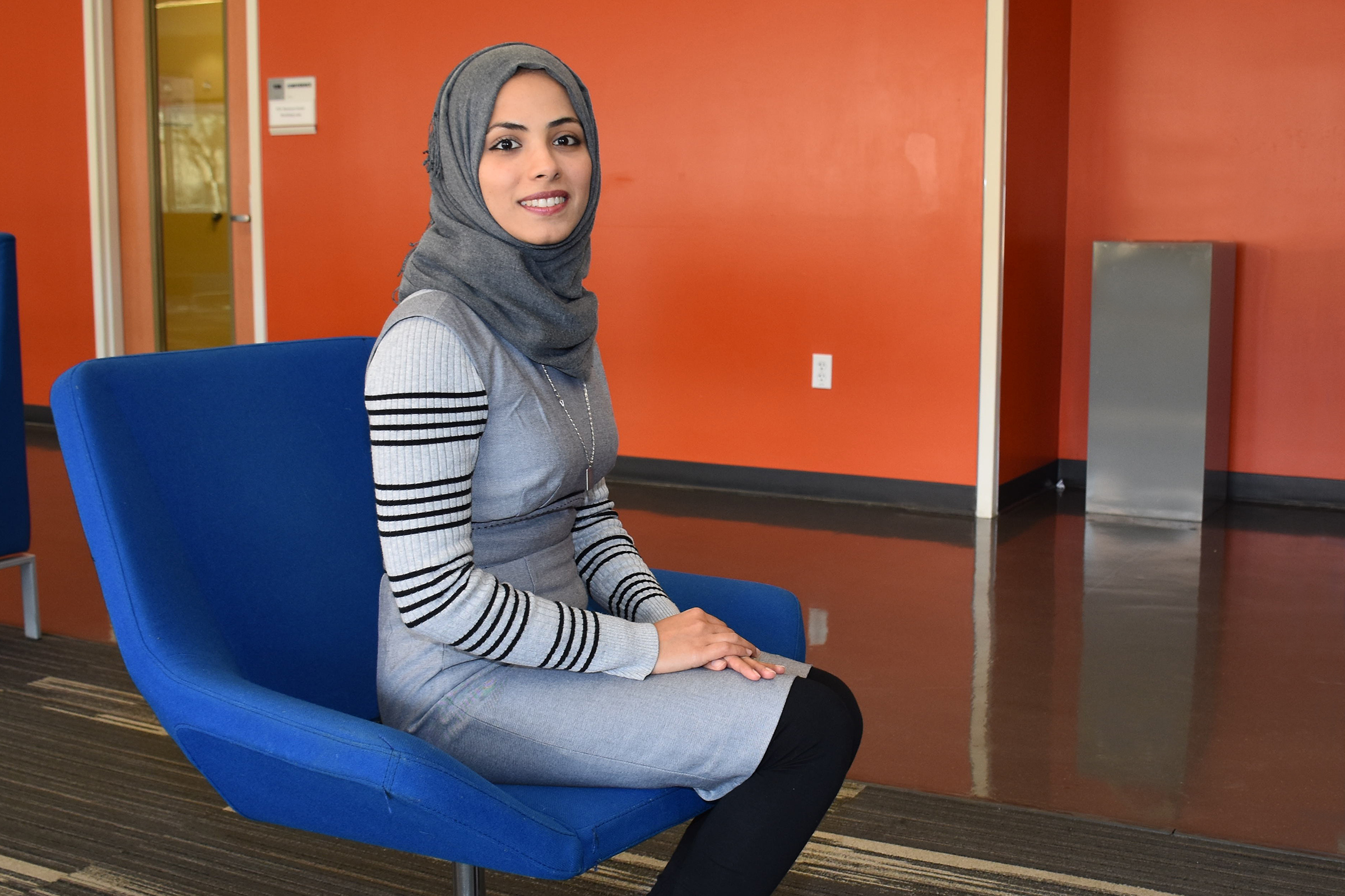 muslim female student sitting and smiling
