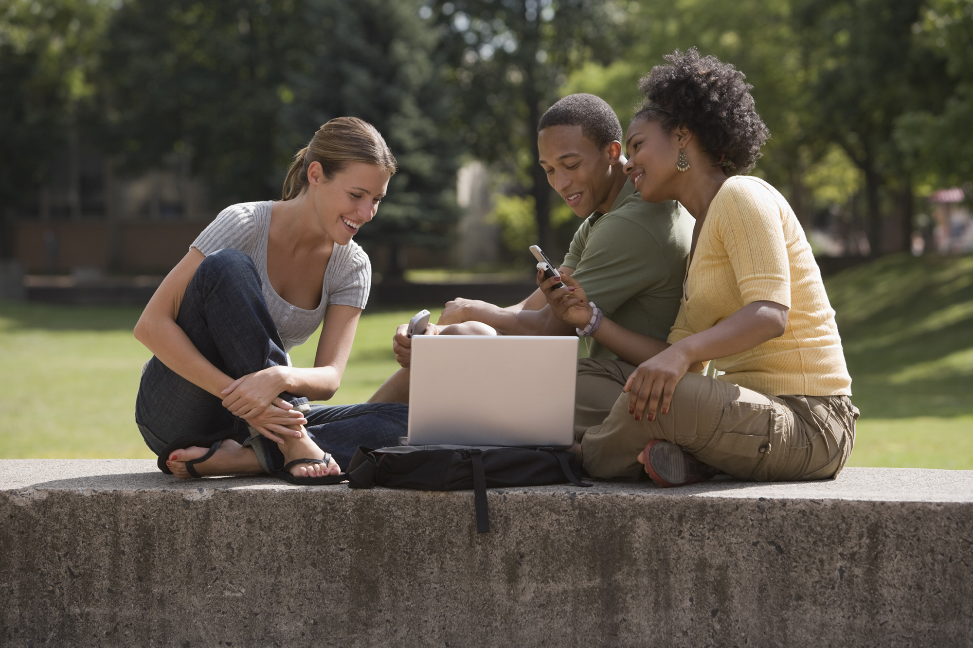 Two female students and one male student sitting outdoors looking at a laptop and phone smiling.