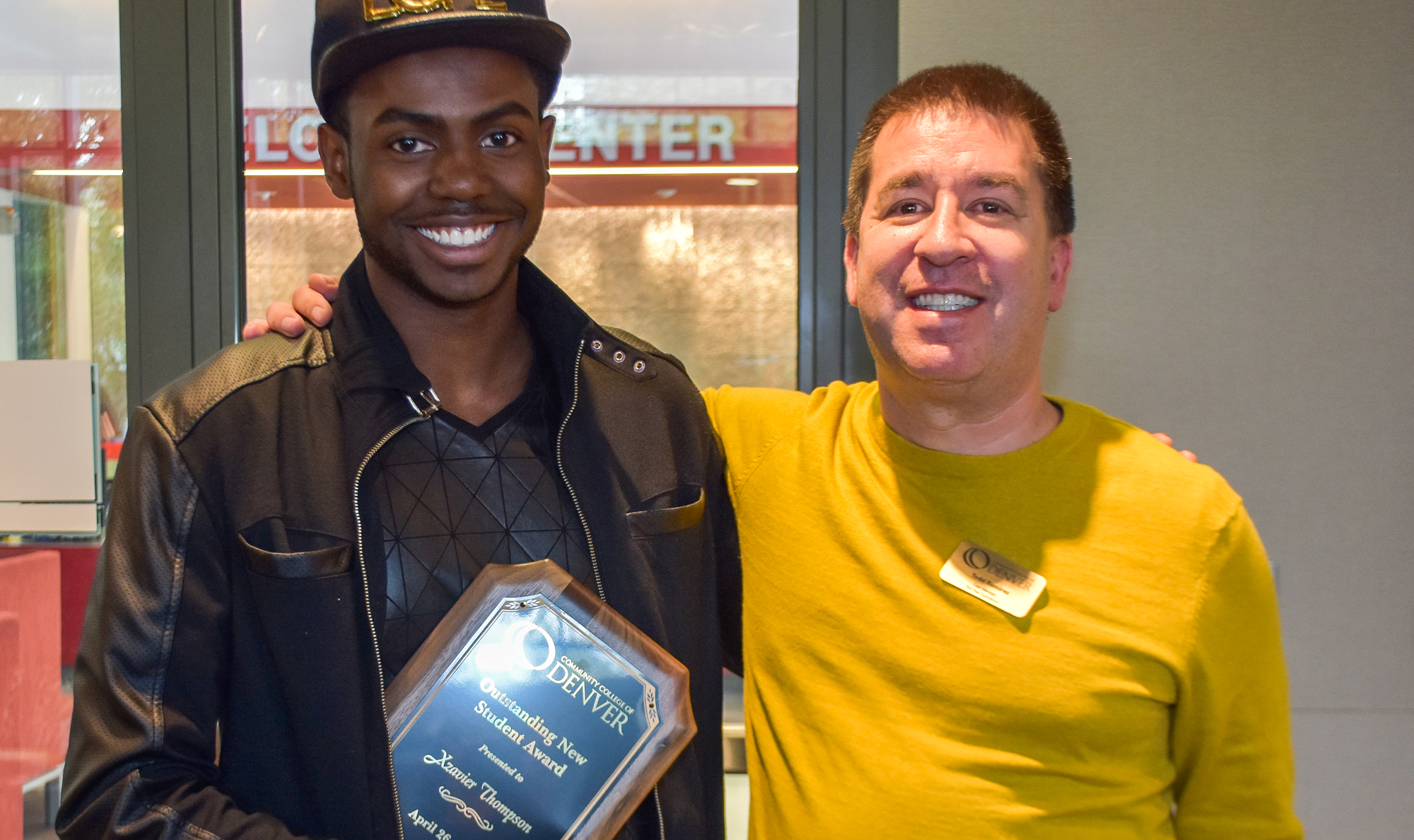 two men smiling, one holding an award