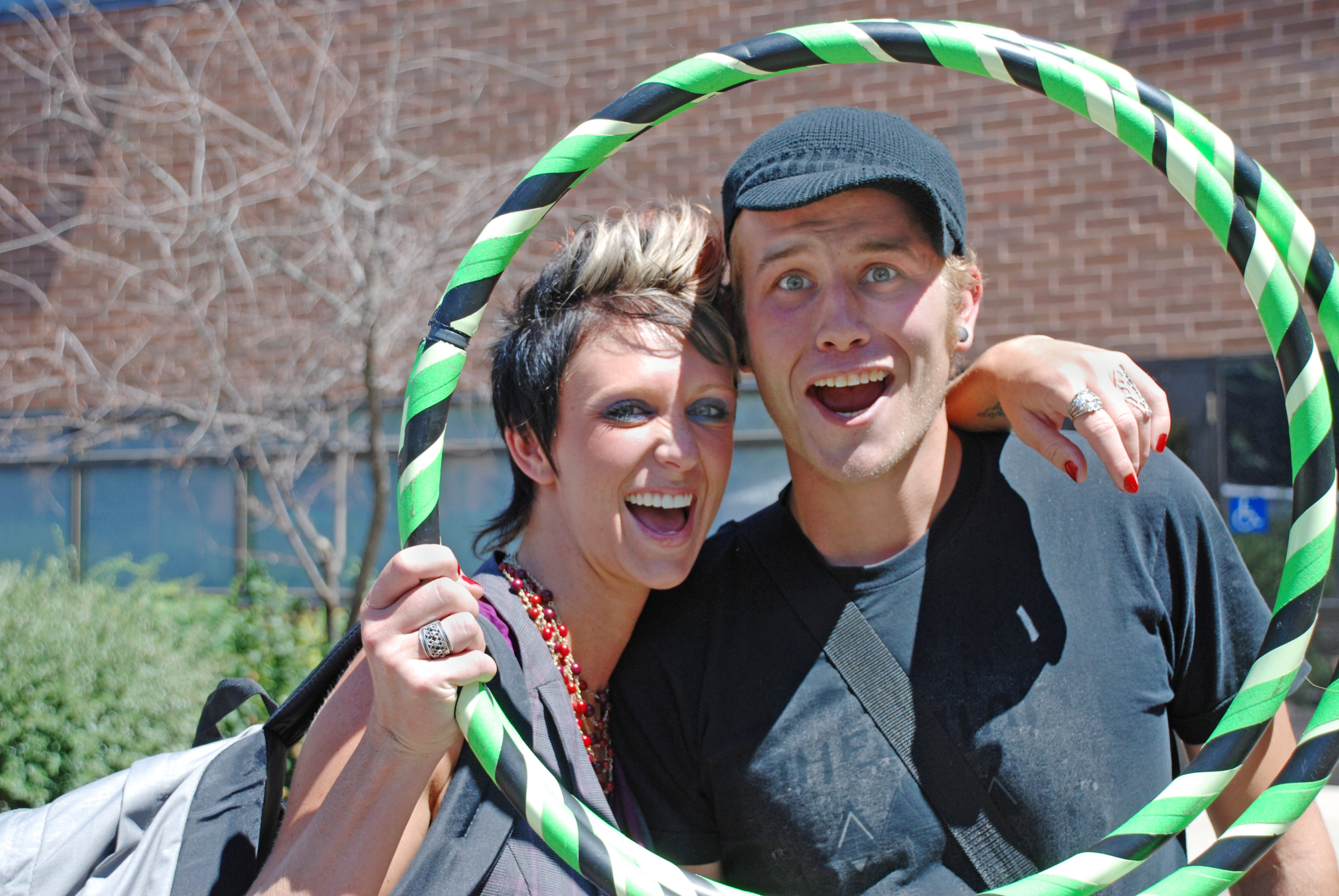 Female and male student smiling and looking through hula hoop