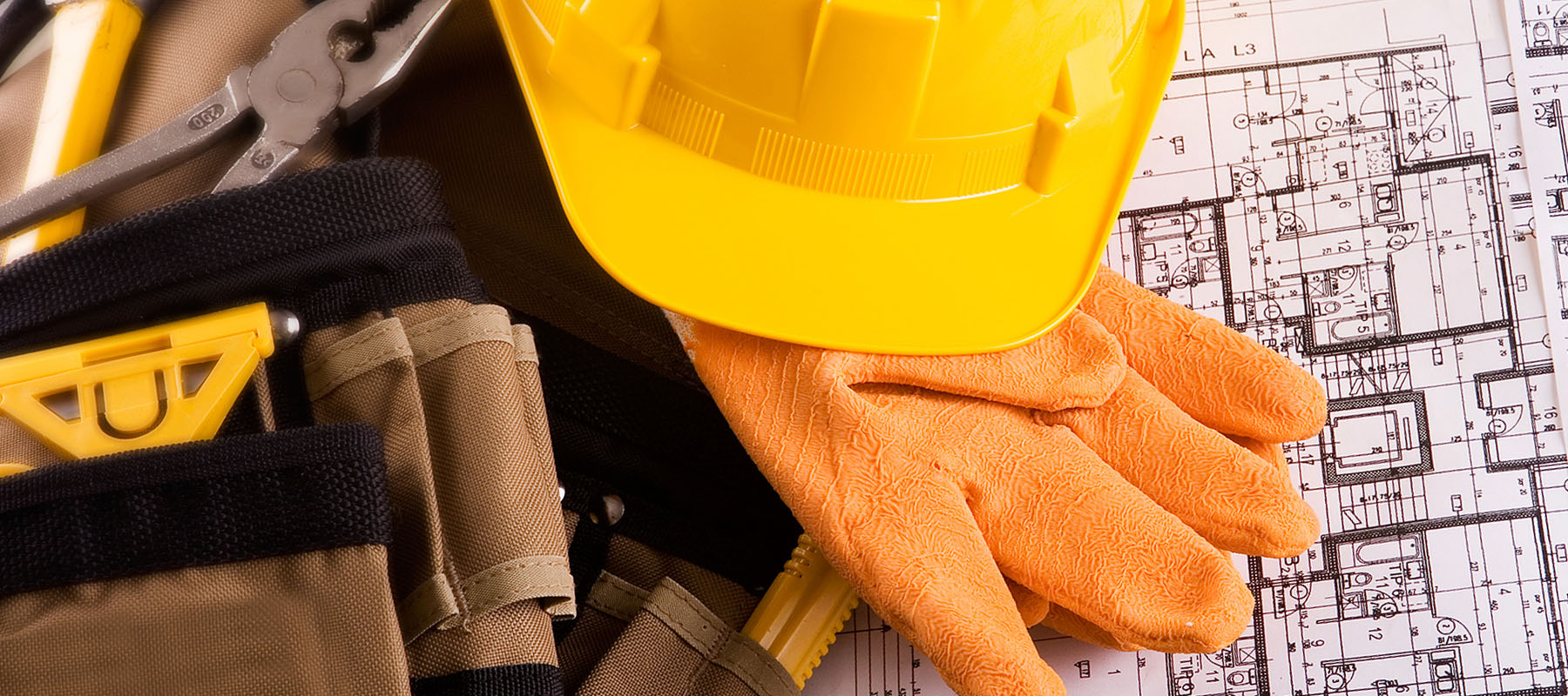 yellow hard hat, work gloves and tool belt next to building plans