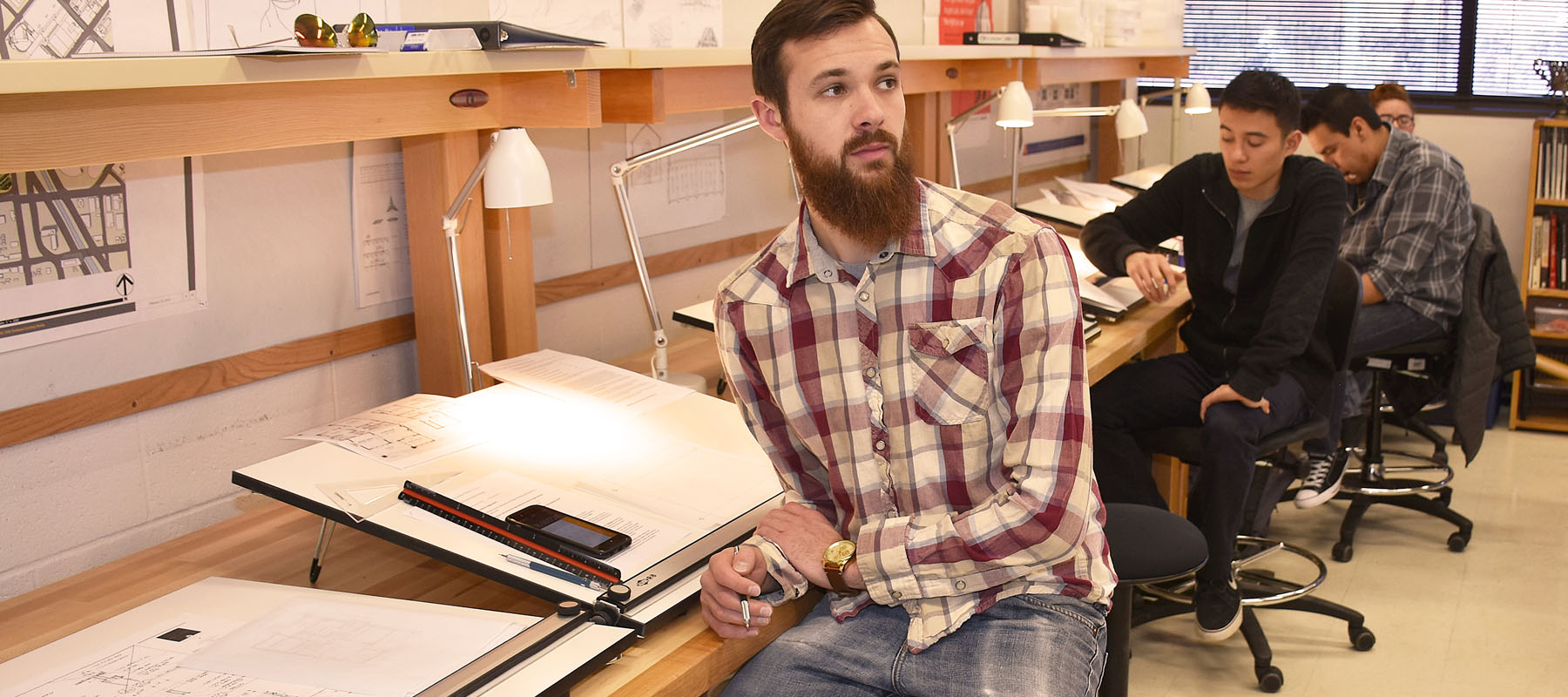 male student sits at a drafting table during class