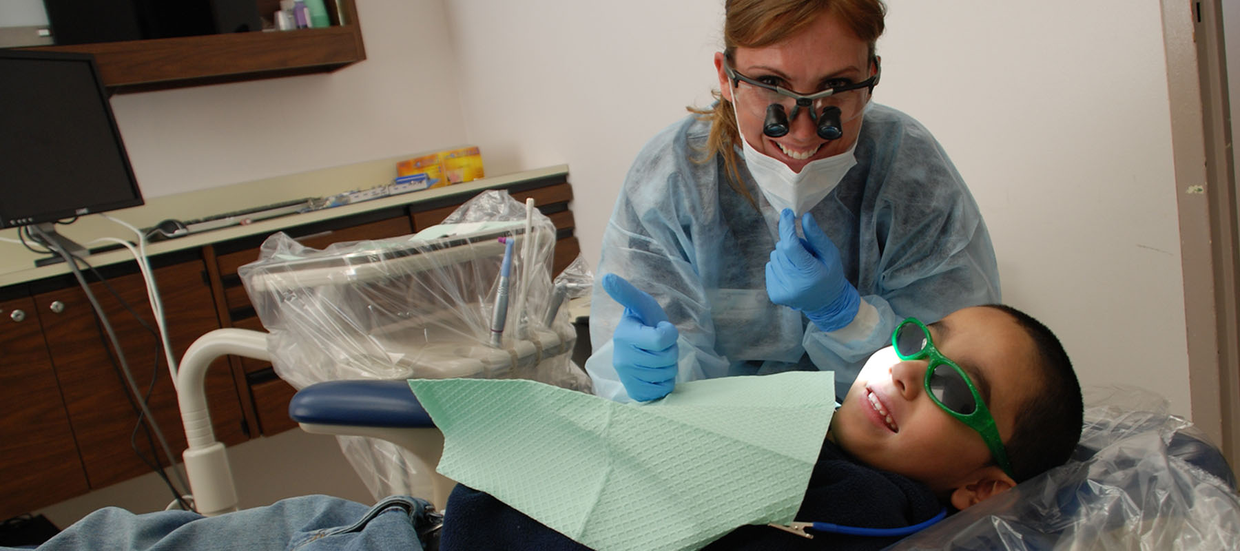 a child with googles on gets his teeth cleaned at the dentist
