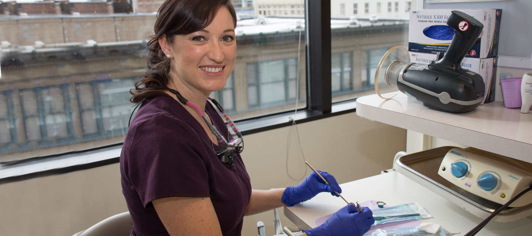 female dental hygenist in purple scrubs