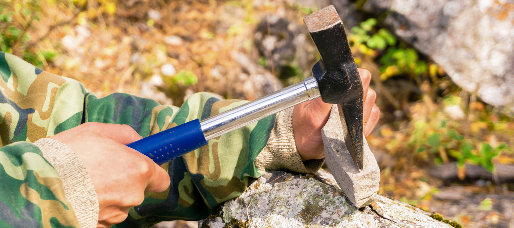 person using a hammer to break open a rock