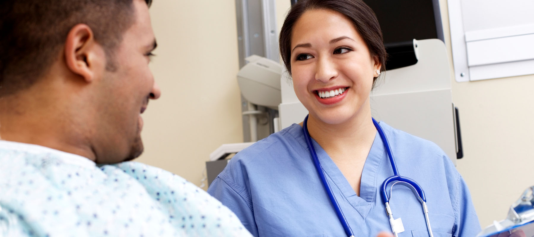 female in blue scrubs speaking with a male patient