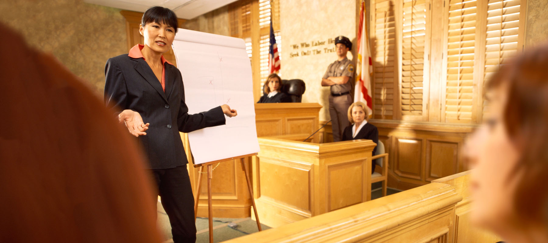 female in a suit talks to a jury in a court room