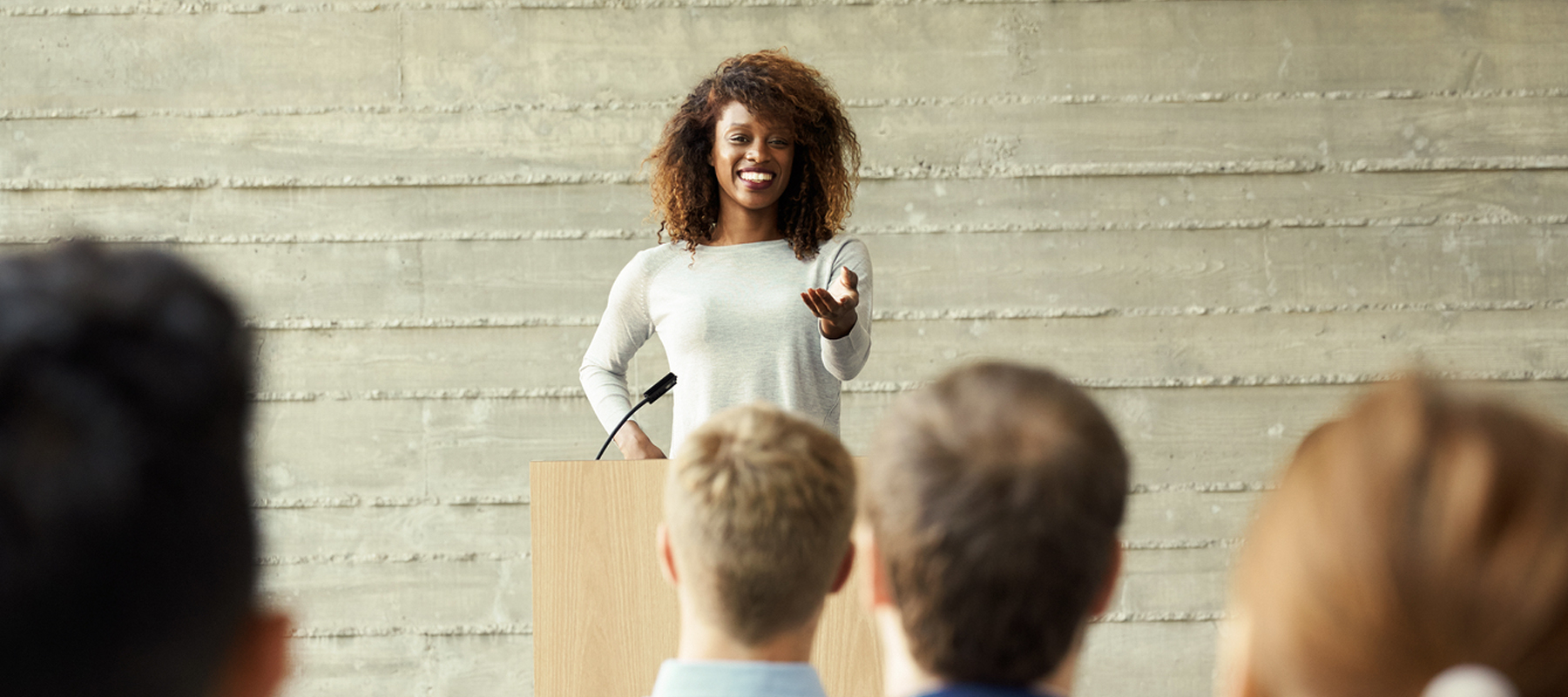 female speaker at a podium in front of a crowd