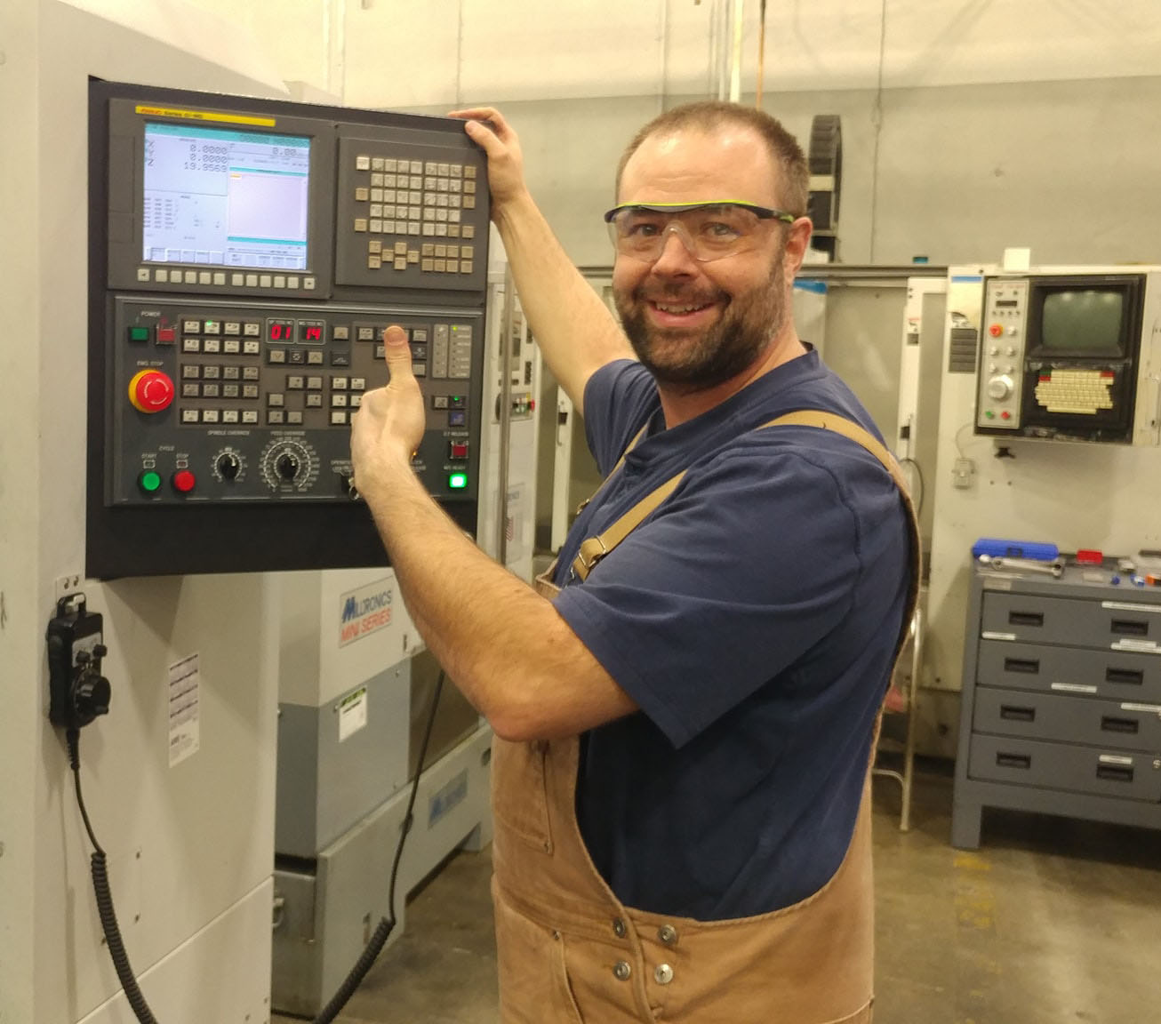 white male standing in front of a CNC maching smiling