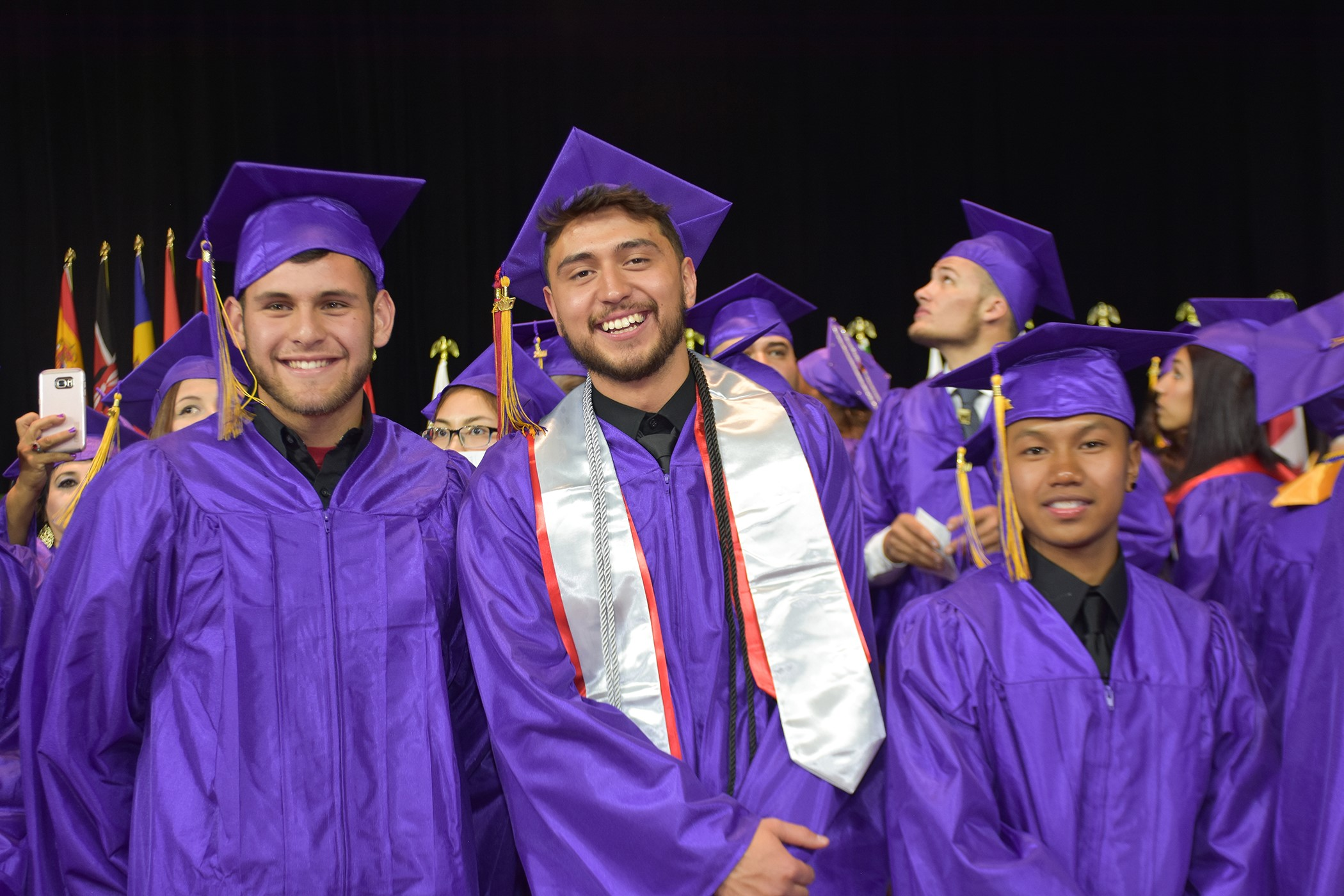 three male grads at commencement in cap and gown
