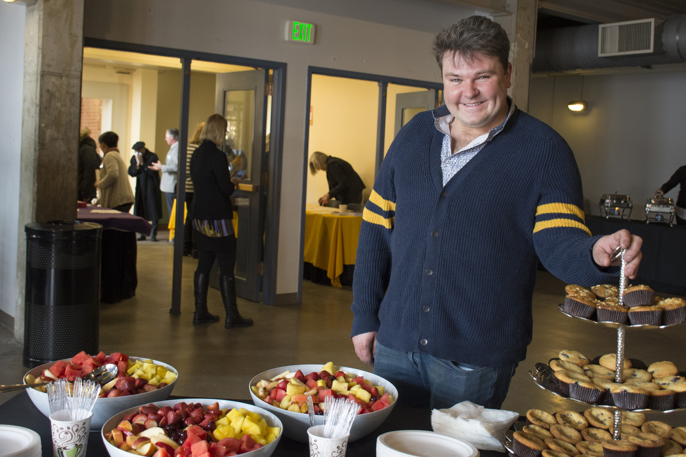 caterer stands next to table of breakfast food