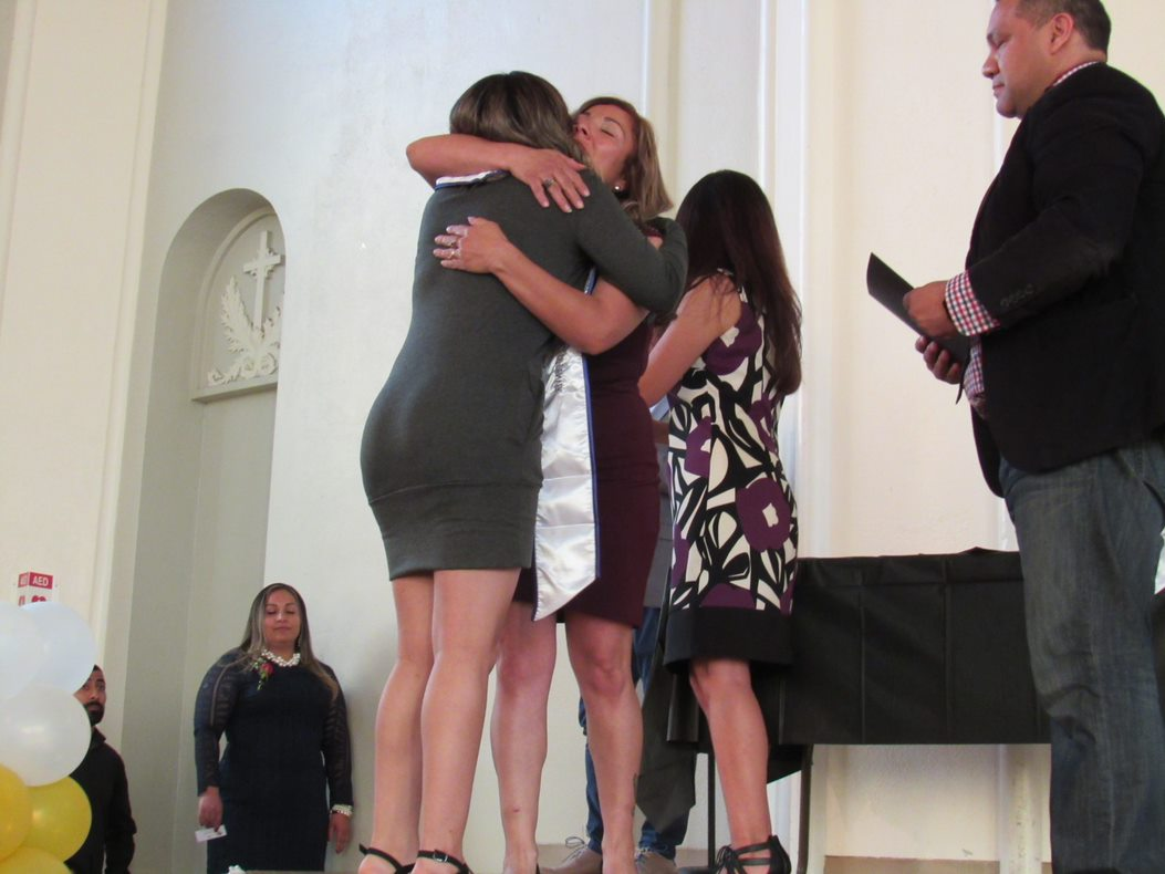 CCD Student being embraced as she walks across the stage while receiving her diploma.