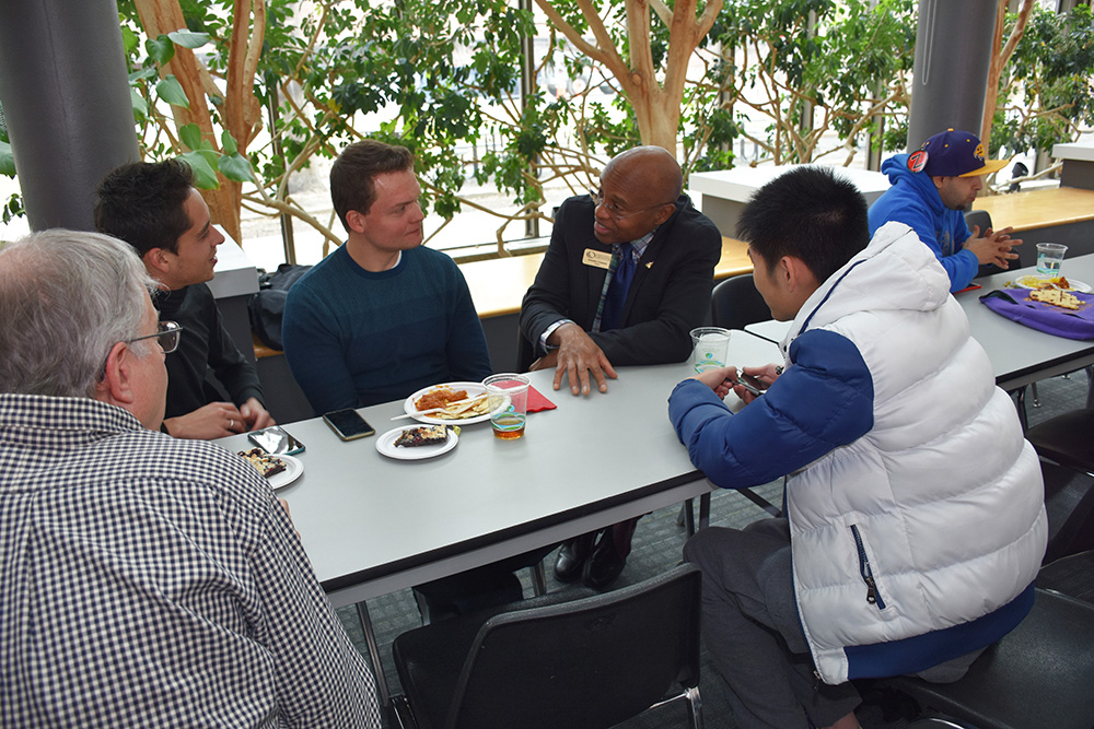 Everette talking to students at a table