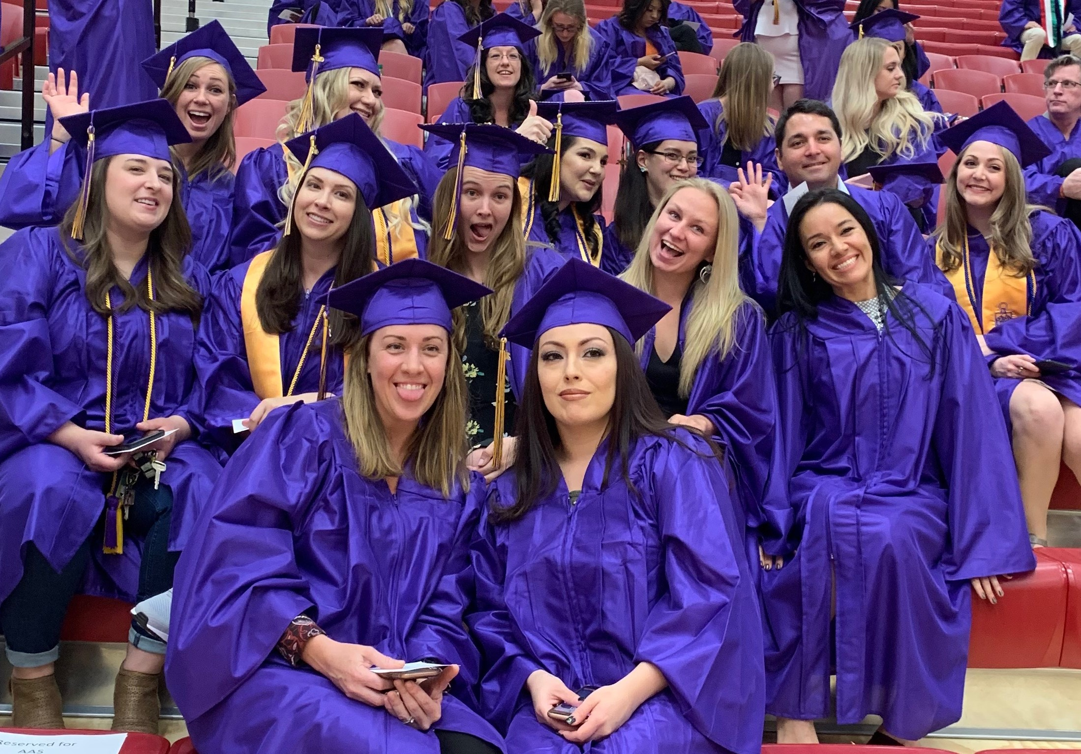 Women waiting to walk out for graduation dressed in purple