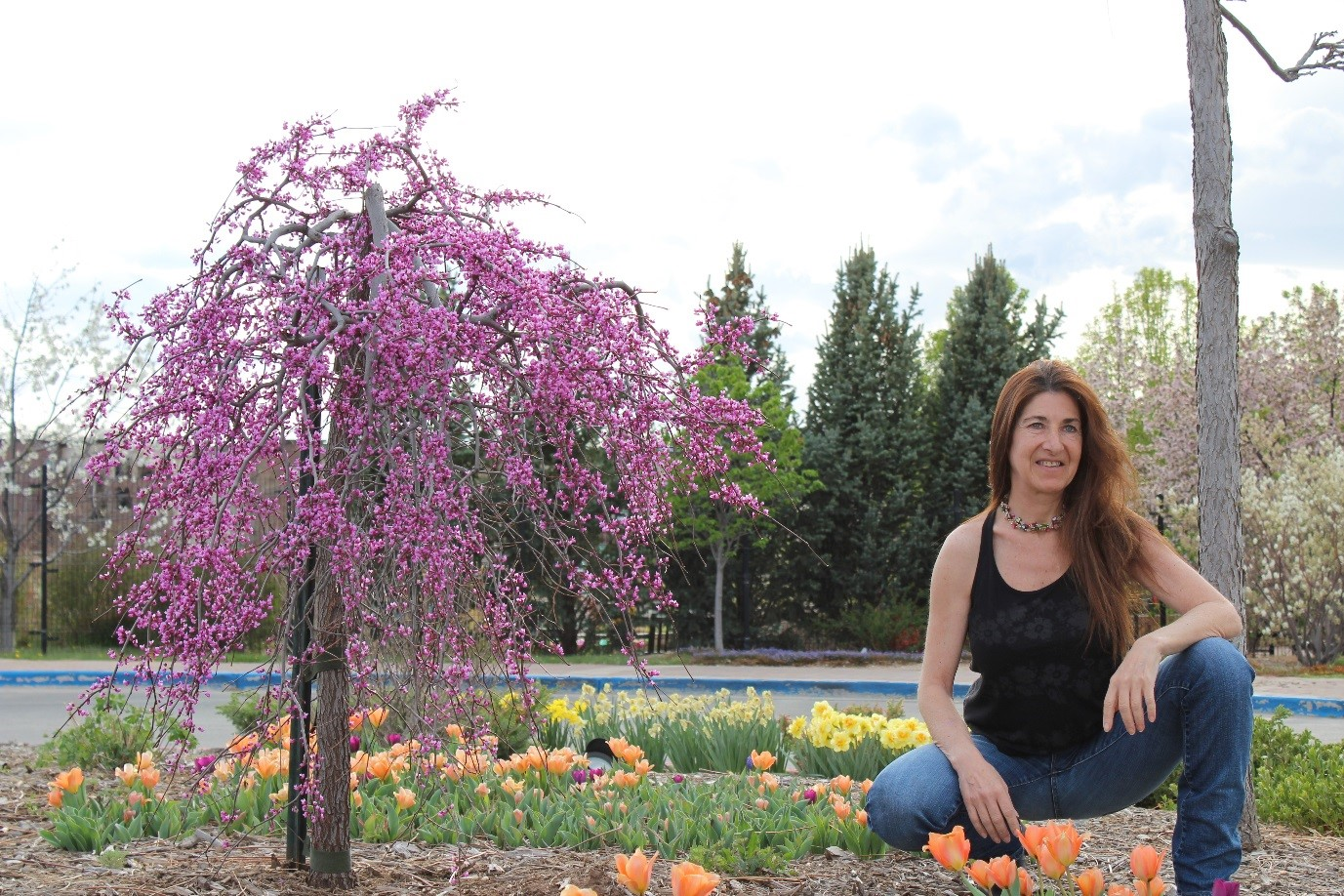 woman sitting outside next to Cherry Blossom tree