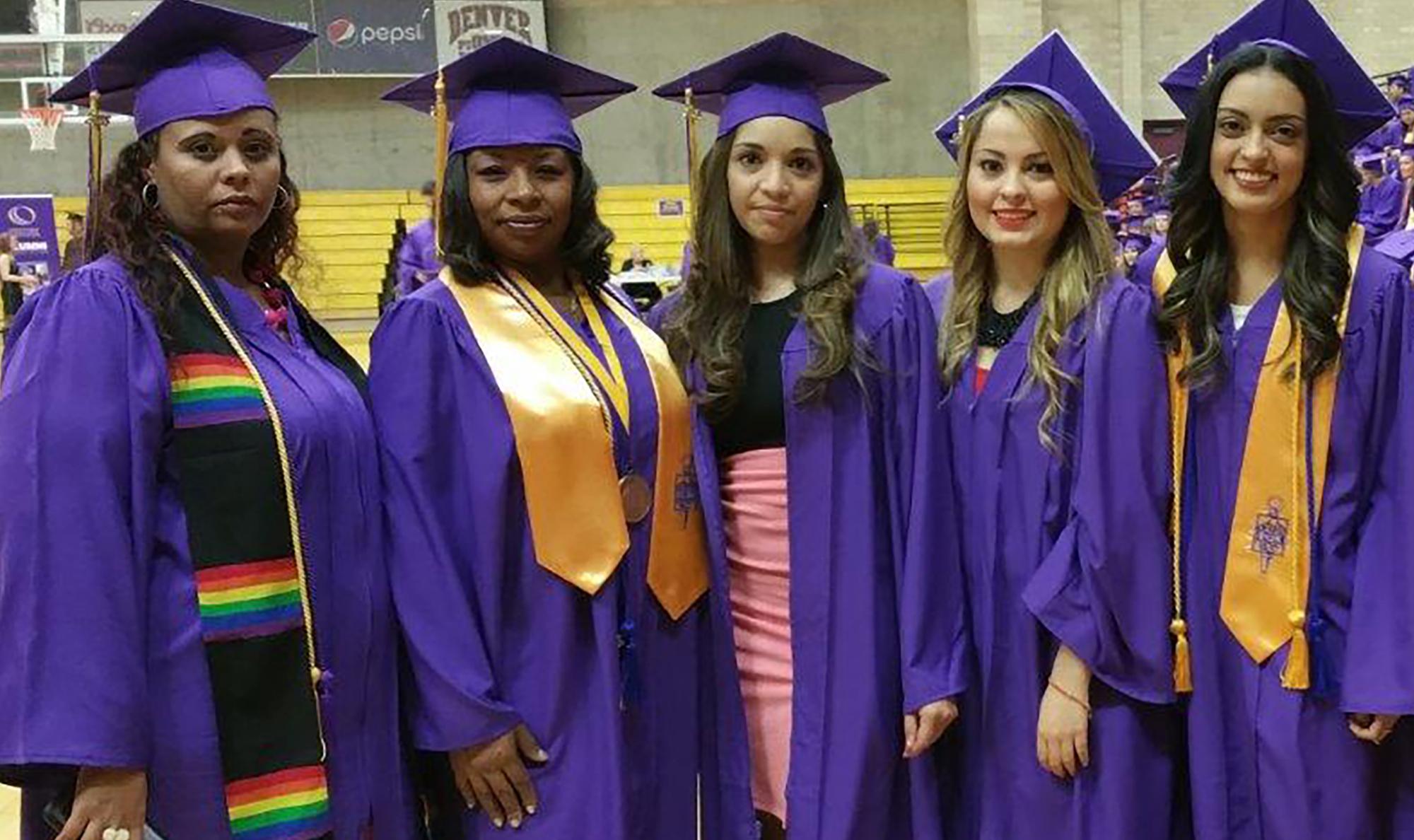 five women in purple cap and gown graduation regalia