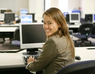 Female student smiling at a computer work station.