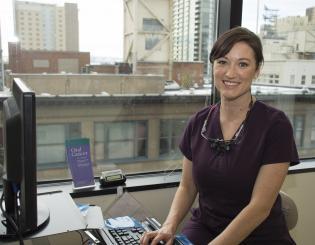 ccd dental student sitting down wearing medical scrubs smiling