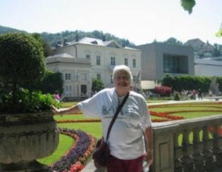 woman standing in front of gardens and large house