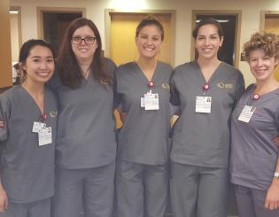 5 young nurse aide students standing in scrubs smiling
