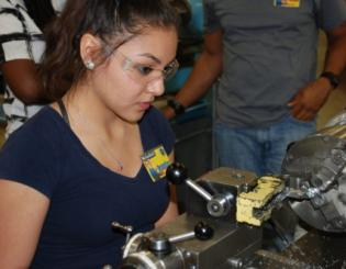 female works on machining equipment