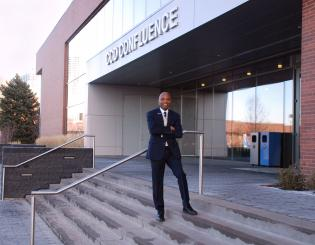 a black man standing on the steps in front of a building