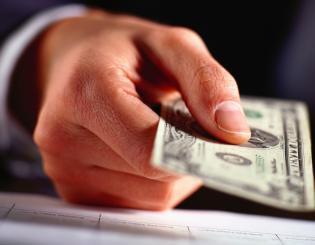 A close up of a hand holding a twenty dollar bill