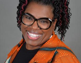 black woman wearing glasses in an orange shirt smiling