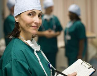 A young nurse wearing green medical scrubs holding a clipboard.