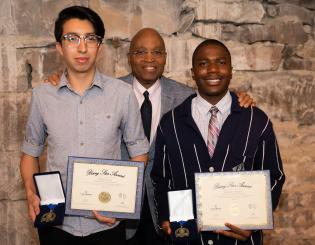 two students holding certificates and awards with the president of the college