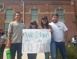 students holding a sign at a rally on the Auraria Campus