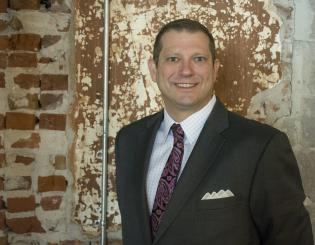 white man in a suit standing in front of a brick wall smiling