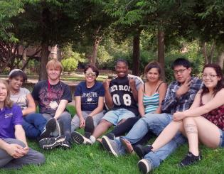 Summer Bridge students sit in the grass.